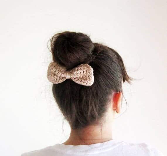 A woman wearing a crocheted hair bow.