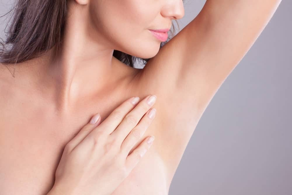 A woman showing off her hairless armpit.