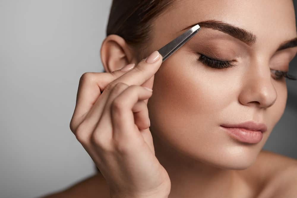A woman plucks her eyebrows with a tweezer.