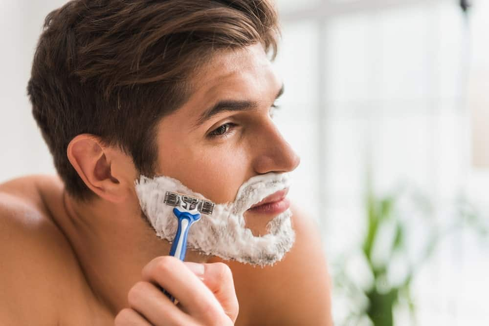 A man shaves his beard with razor and cream.
