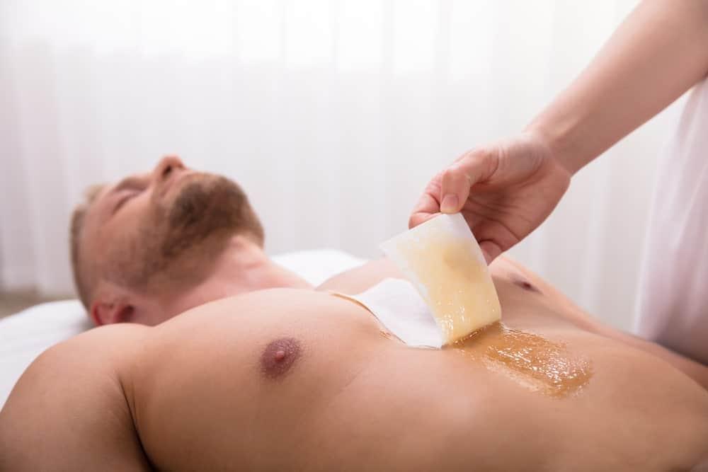 A man undergoing chest waxing.