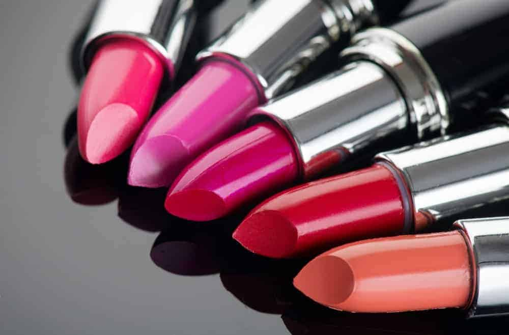 Different colorful lipsticks on display on a black surface.