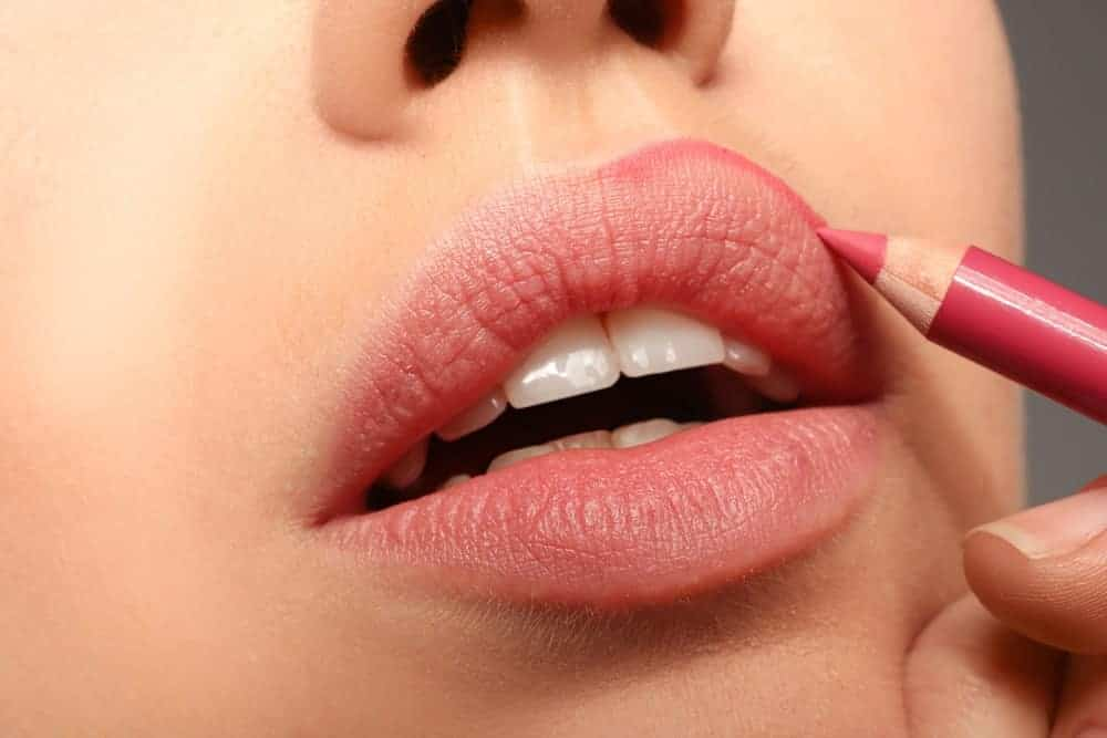 Woman applying lipstick pencil on her lips.