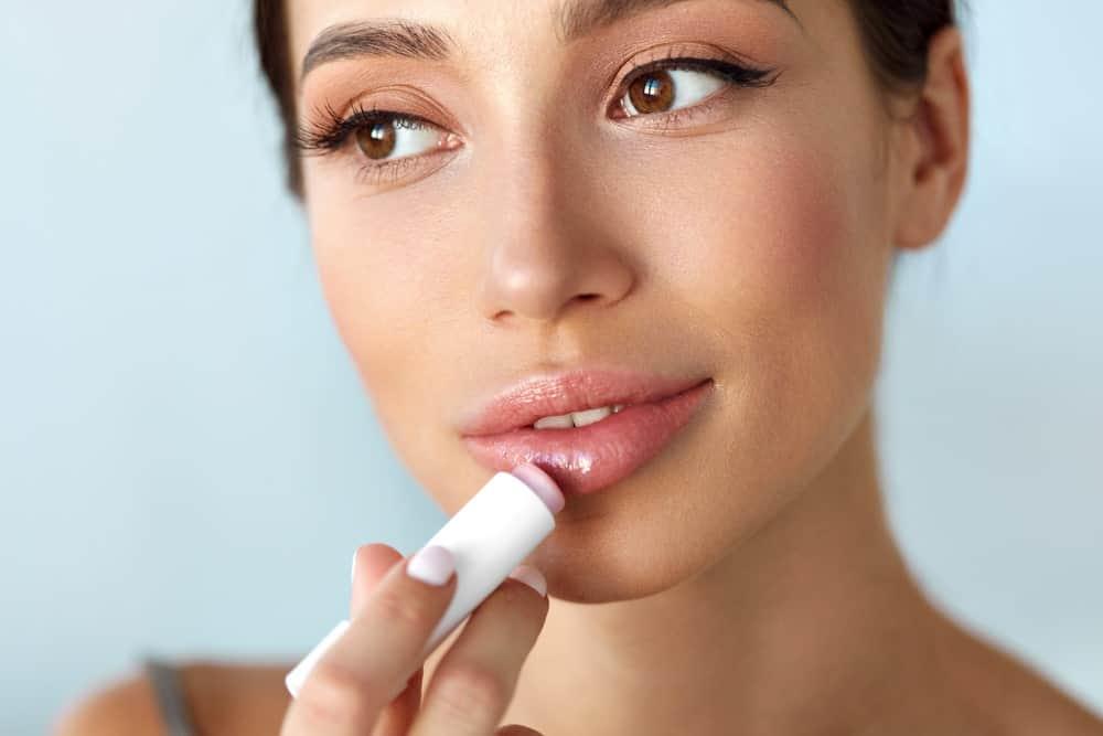 A woman putting on moisturizing lipstick.