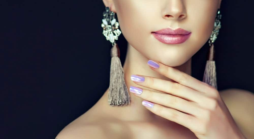 A woman with dangling earrings and colored nails wearing pearl lipstick.