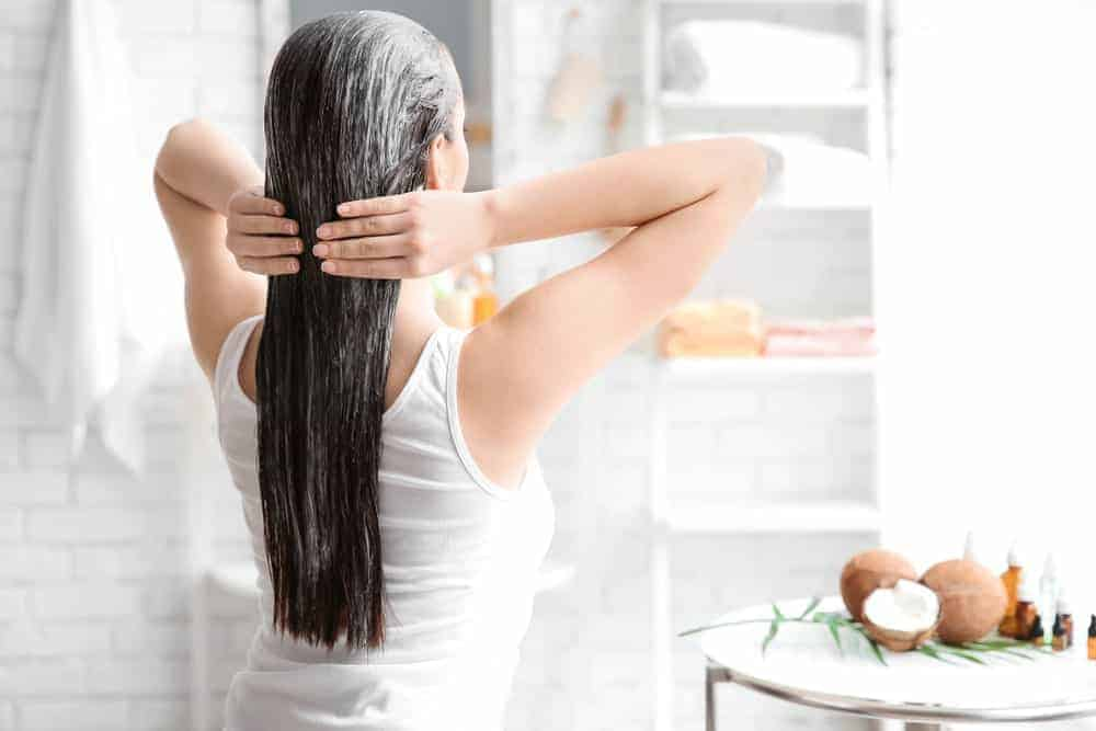 A woman oiling her hair in the bathroom.