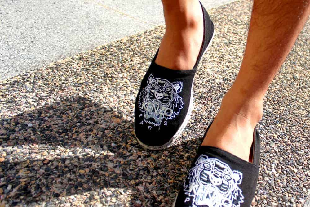 A man wearing a pair of Black Espadrille Loafers with a tiger-face design.