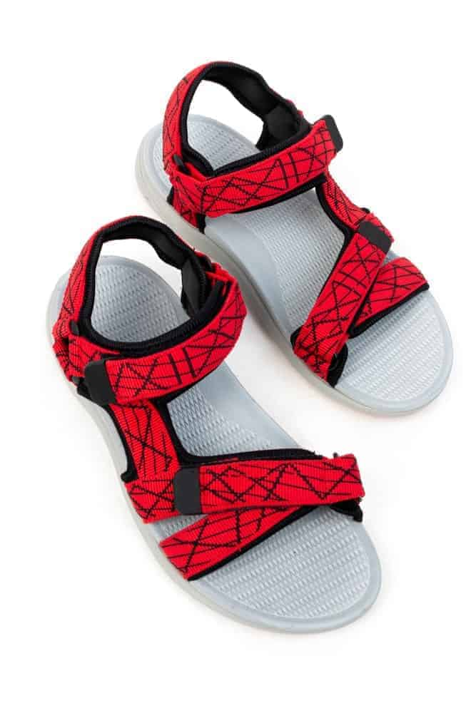 A pair of gladiator sandals with red straps.