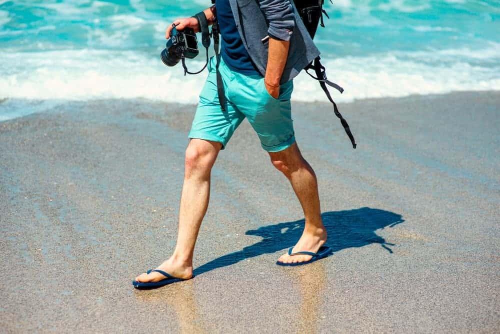 A man sporting beach attire and flip flops.