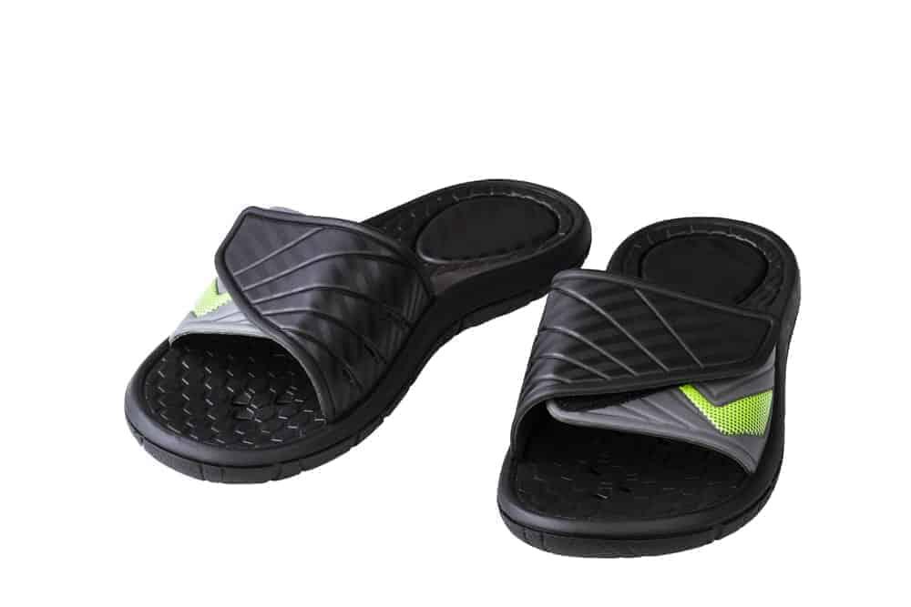 A pair of black slide sandals for men.