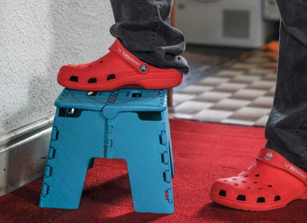 A man wearing red crocs and black denim jeans.
