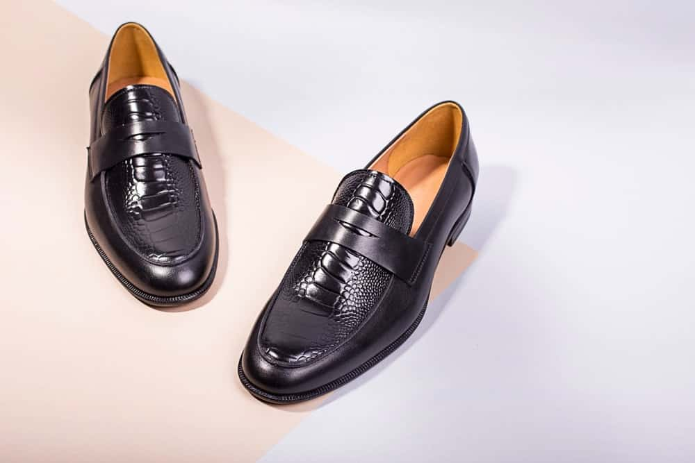 A pair of black leather loafers on a bright surface.