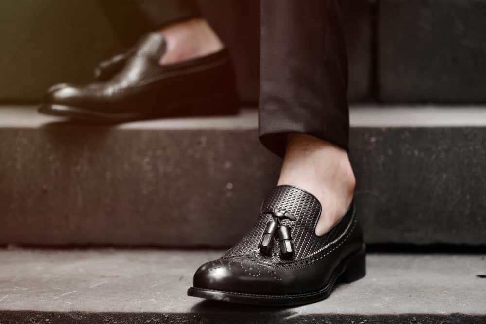 A man wearing black tassel loafers on gray stairs.