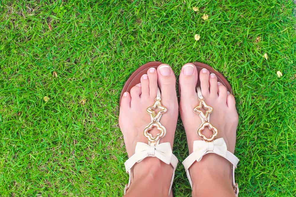 A woman wearing a pair of white thong sandals with golden embellishments.