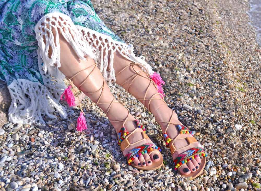A woman wearing a pair of gladiator sandals at the beach.