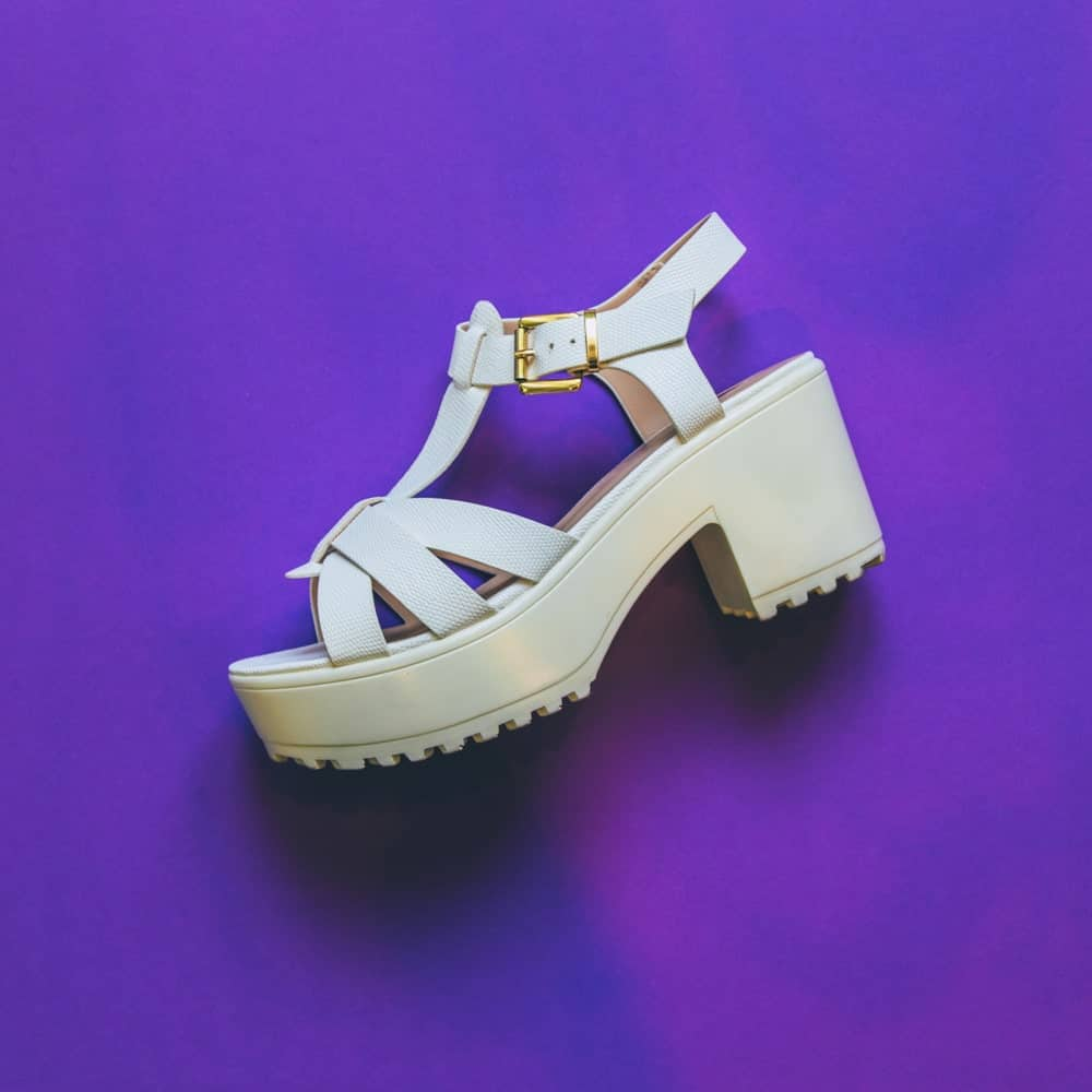 A white platform sandal on a purple surface.