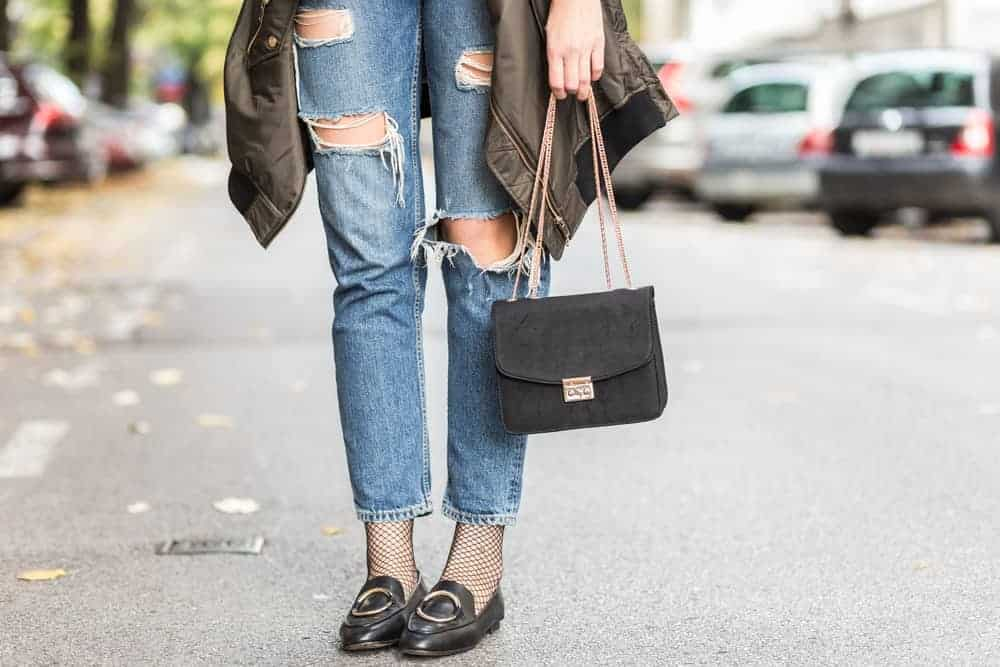A woman wearing ripped jeans and a pair of trendy black loafers.