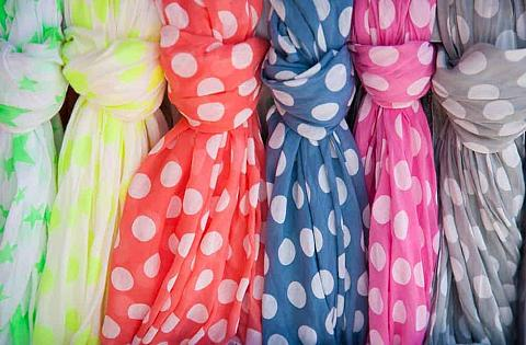 A row of colorful, dotted cotton scarves.