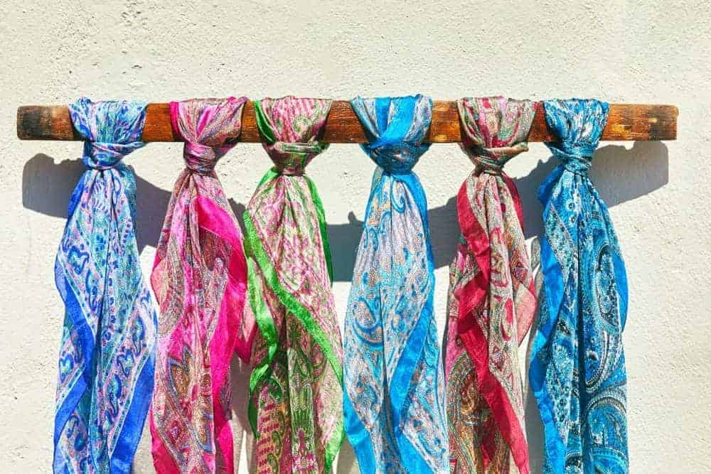 Six colorful silk scarves with intricate designs.