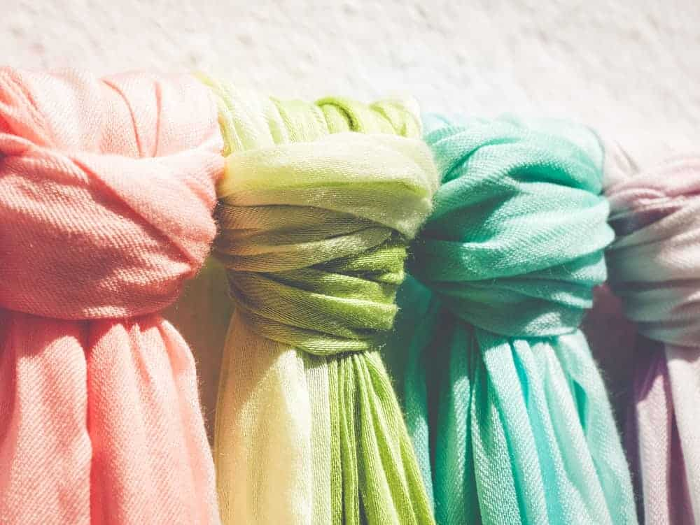 Colorful pashmina scarves in a market on display.
