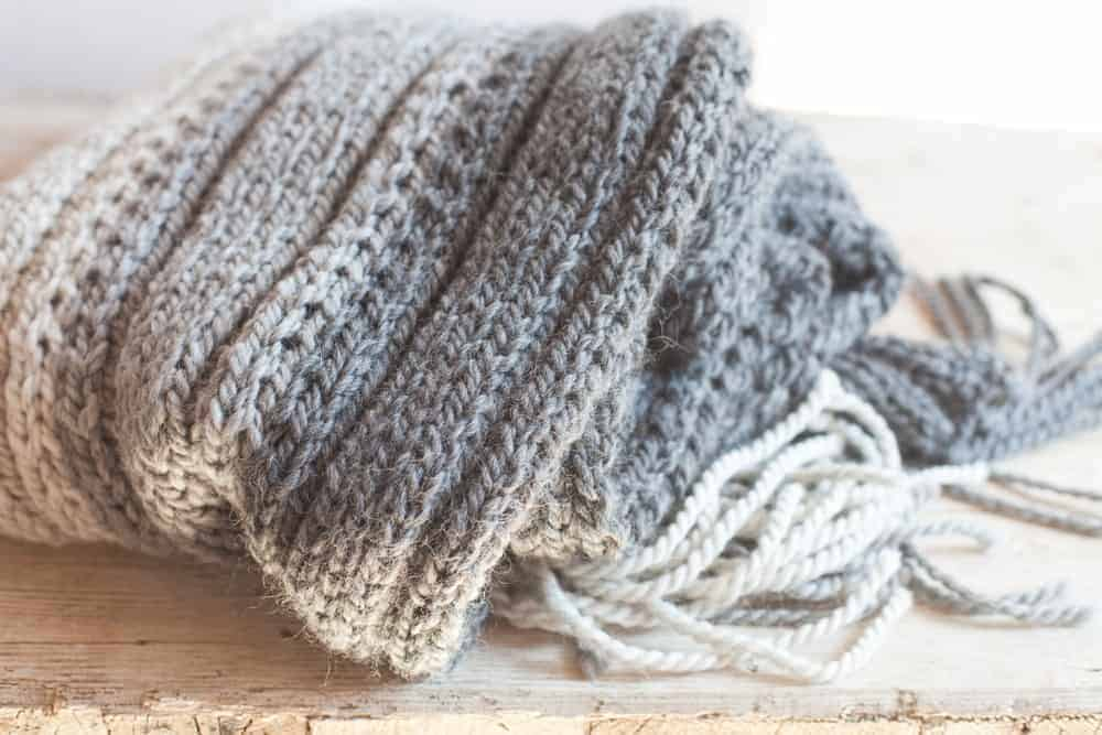 Gray and white wool scarf on a wooden surface.