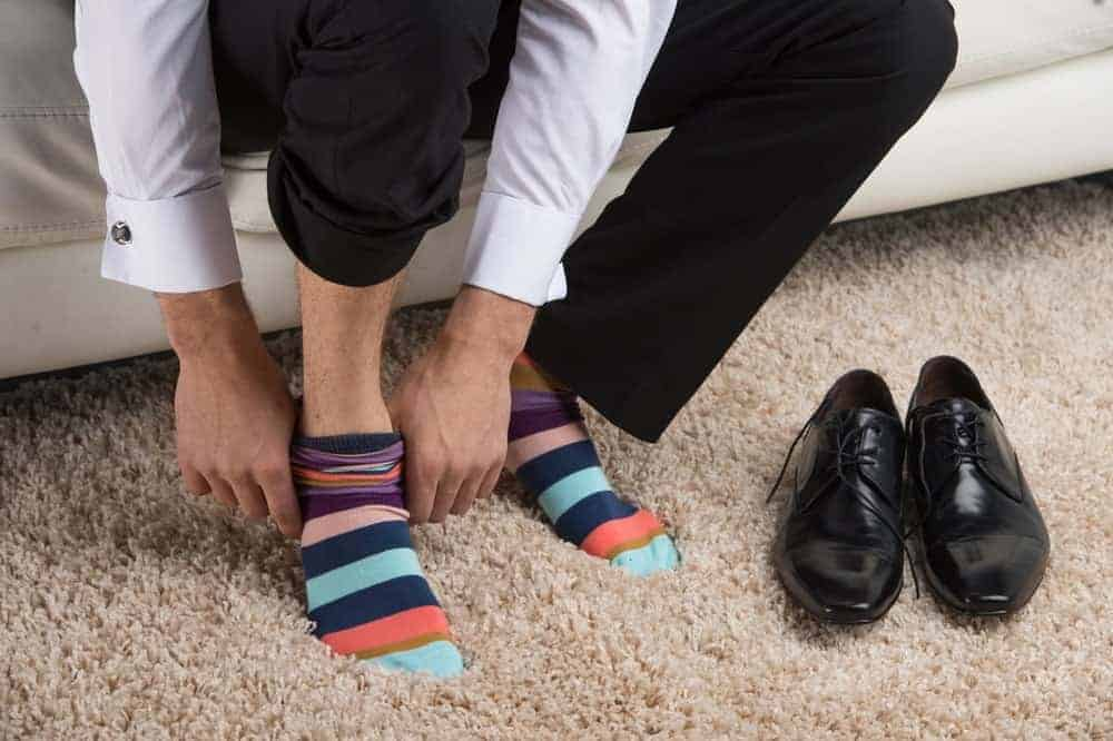 A man putting on a pair of colorful, striped socks.