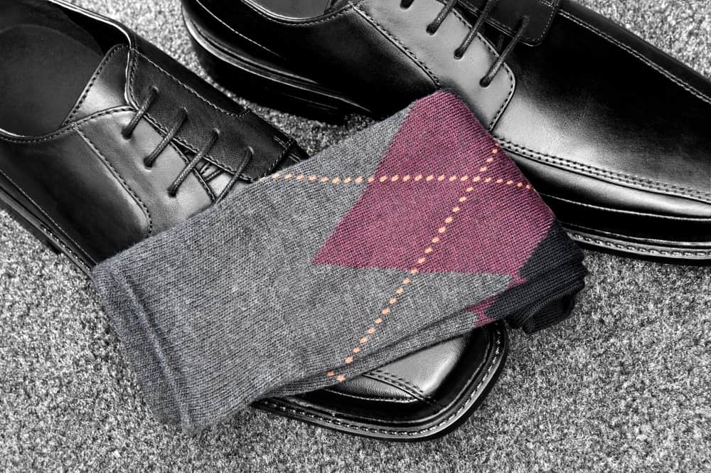 A nice pair of gray socks with formal black leather shoes.