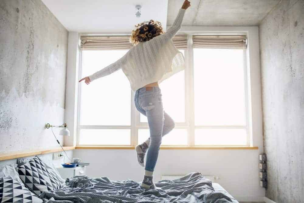 Woman in white sweater jumping on bed.