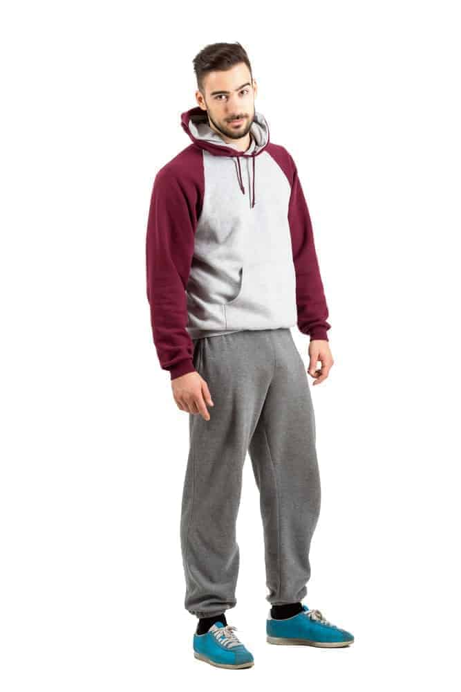 A man wearing a pair of gray baggy sweatpants.