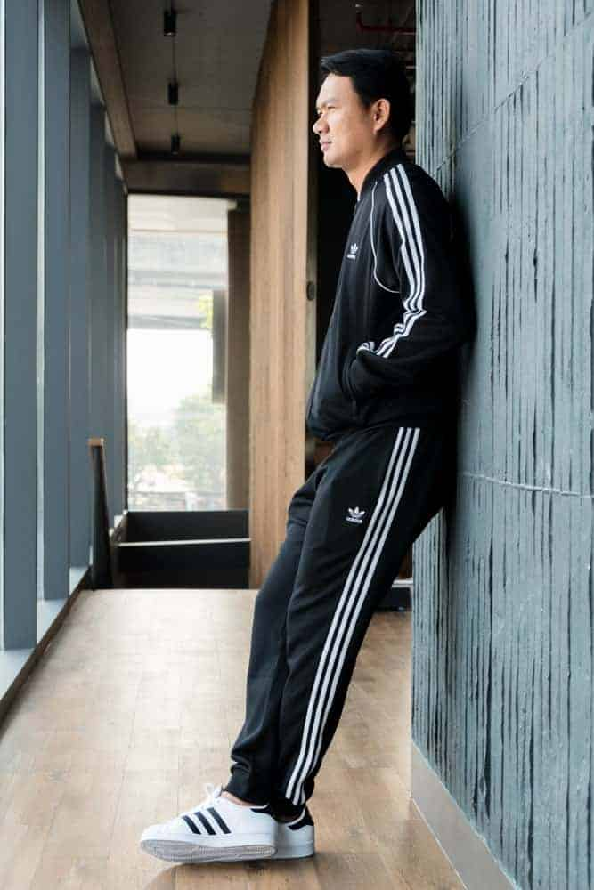 A man wearing a pair of black striped sweatpants.