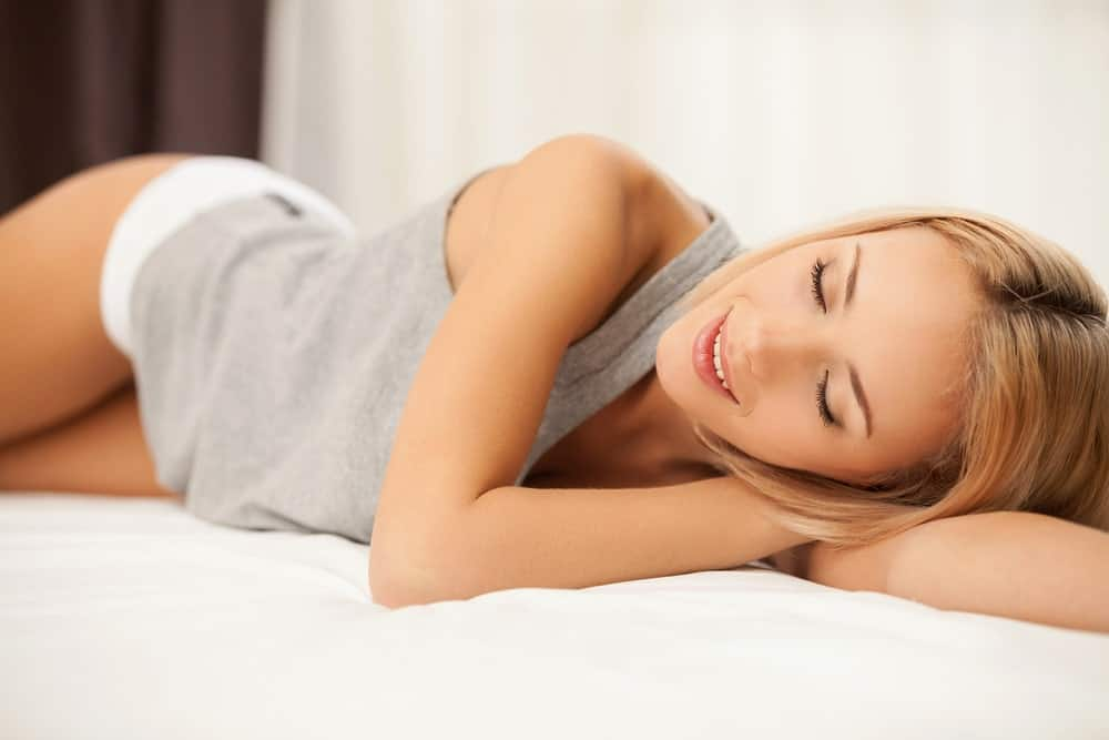 Woman wearing tank tops and short shorts while resting on bed.