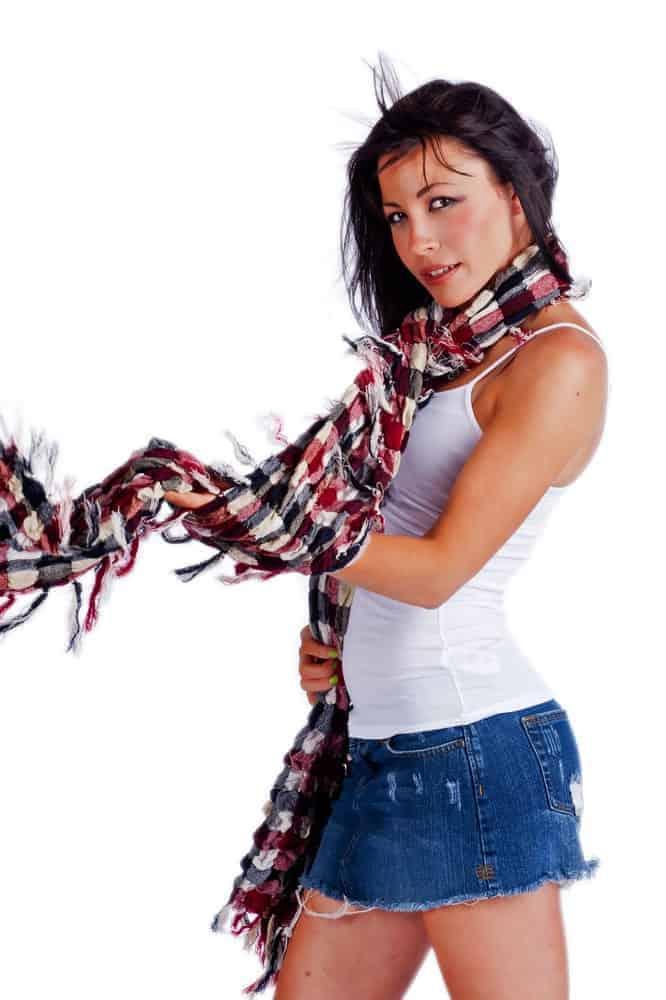 Woman wearing a long scarf, tank tops, and short shorts.