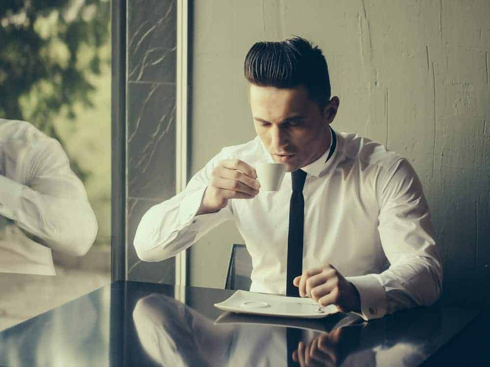 A man drinking coffee while wearing a skinny tie.