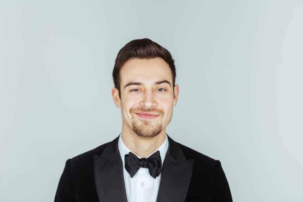 A man wearing a cravat necktie worn with a dinner jacket.
