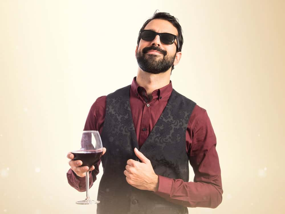 A man wearing a vest with a glass of wine.