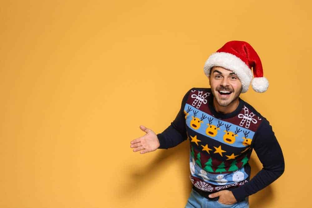 Man against an orange backdrop wearing a Christmas hat and an ugly Christmas sweater.