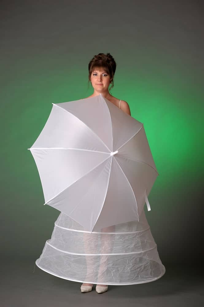 Woman in a white petticoat holding an umbrella.