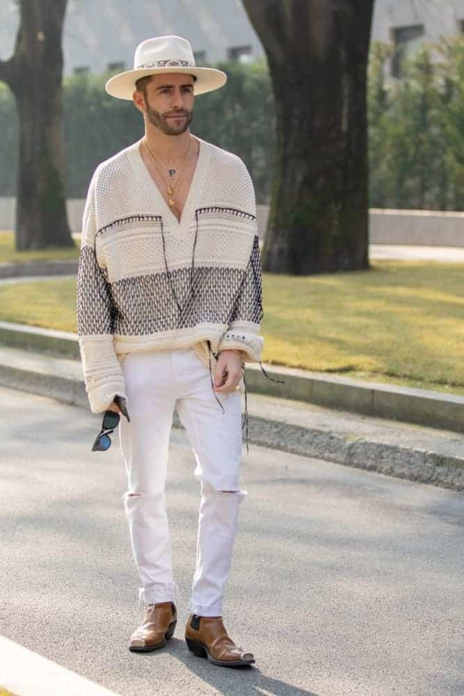 Model wearing a V-neck sweater, white pants, and a Panama hat.
