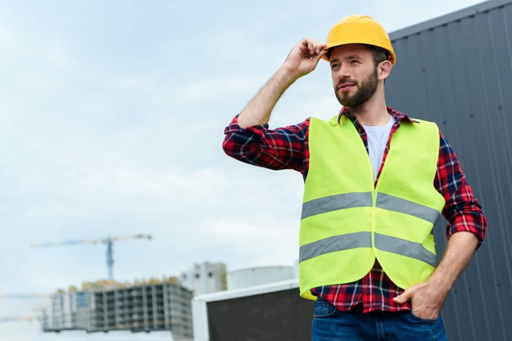 Engineer in safety vest and helmet posing on roof.