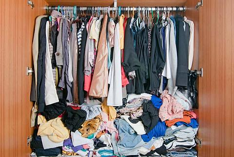 Wardrobe filled with pile of clothes.
