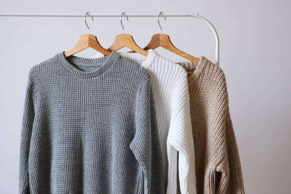 Warm sweaters hanging on a white rack.