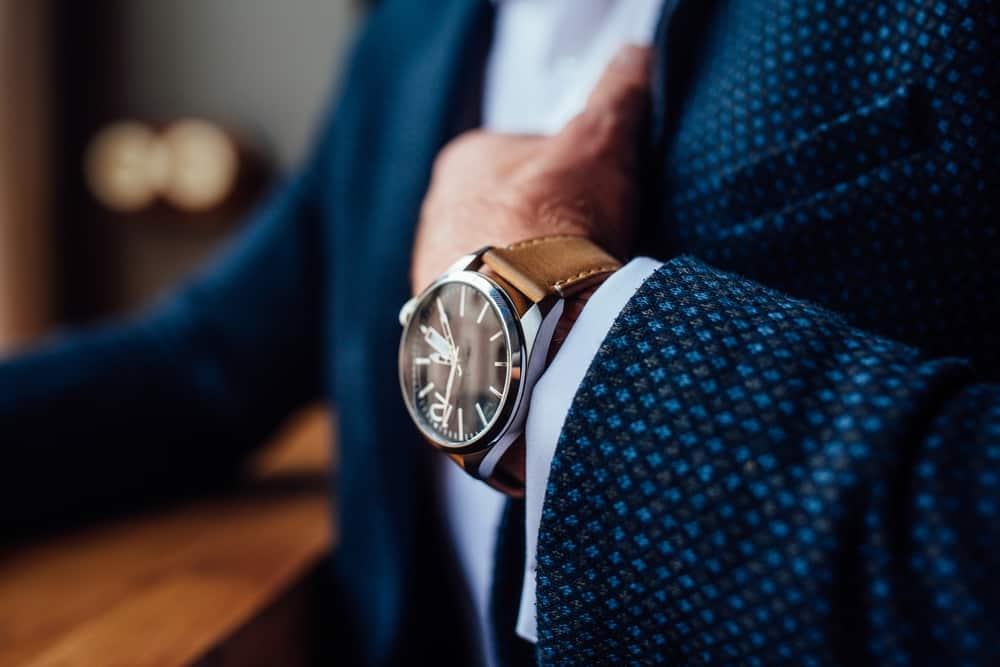 Man in a formal coat wearing watch.