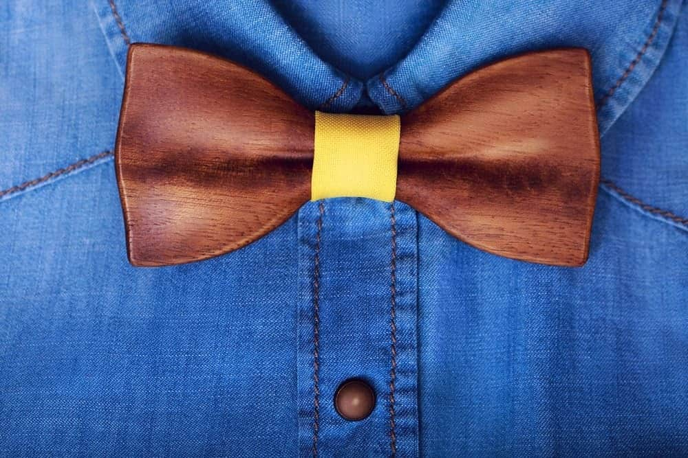 A closer look at a blue shirt paired with a brown western bow tie.