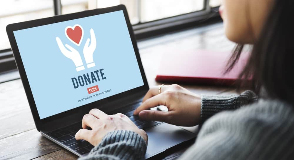 A woman browsing her laptop for ways to donate.