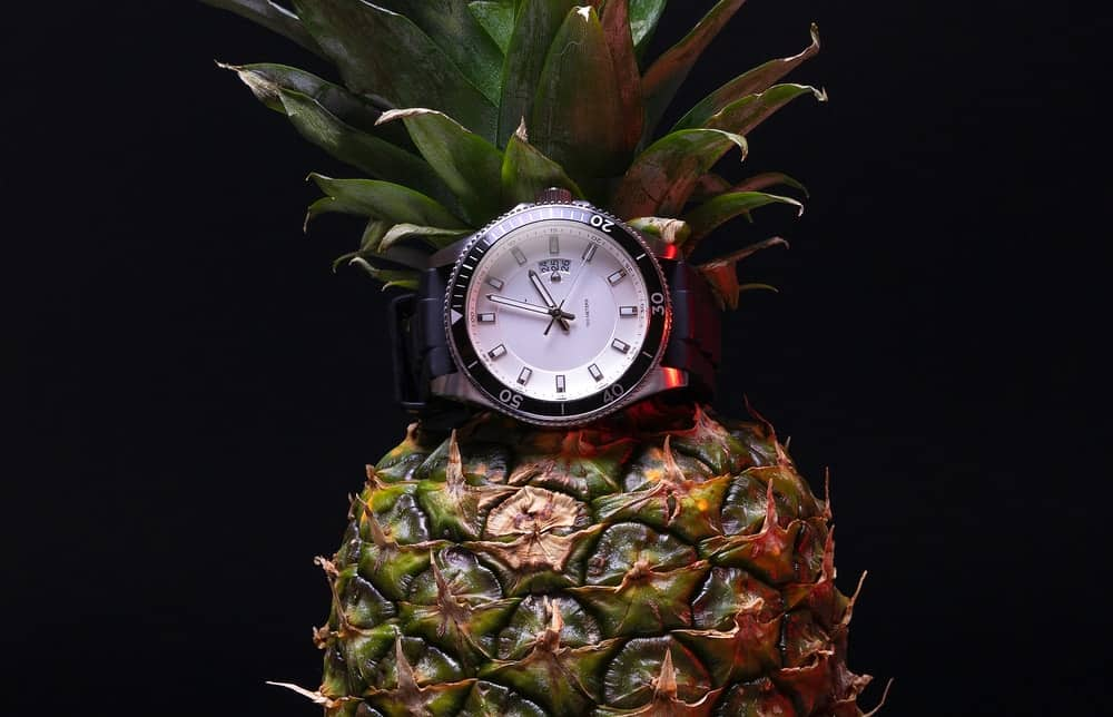 A pineapple fitted with a wrist watch.