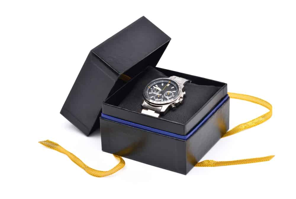 A brand-new watch inside a black box with a gold ribbon.