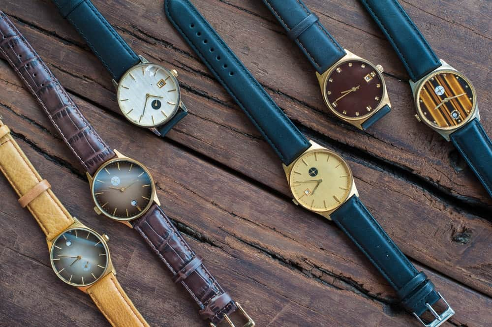 A bunch of vintage wrist watches on a wooden surface.