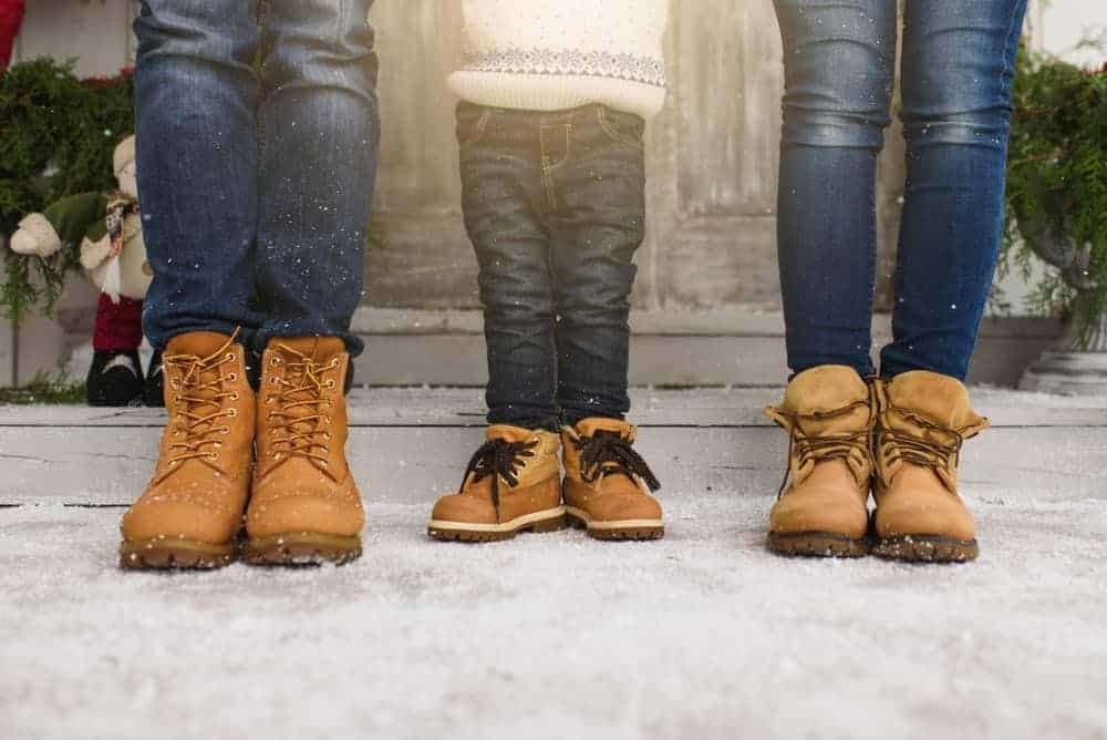 Cropped photo of a family showing their legs with denim pants and winter boots.