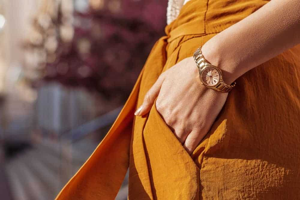 Woman in orange dress with gold watch.