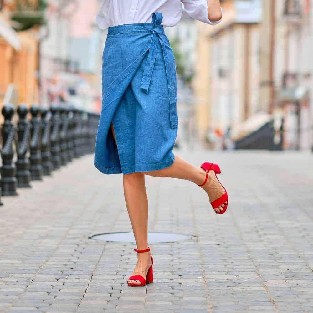Woman wearing a blue wrap skirt and a pair of red heels.